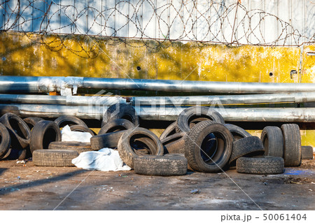 Old car tires are piled up against a fence  50061404