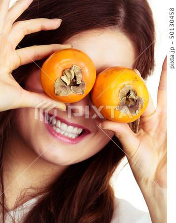 Woman holds persimmon kaki fruits on eyes, 50130458