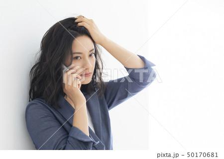 髪をかきあげるミドル女性 50170681