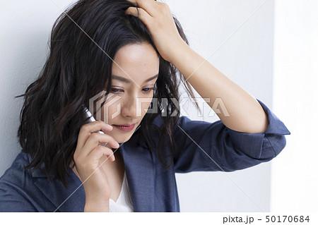 髪をかきあげるミドル女性 50170684