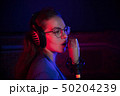 A young woman in glasses singing by the microphone in neon lighting 50204239