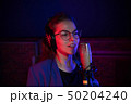 A young pretty woman in glasses singing in neon lighting 50204240