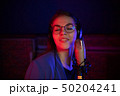 A young woman in glasses singing in neon lighting 50204241