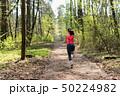 Female runner run in spring sunny forest 50224982