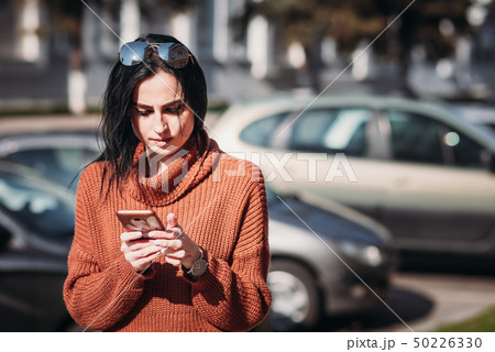 Woman in city street use smartphone 50226330