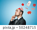 Side close-up of young handsome businessman rubbing chin, upper part of head cut off, with cards 50248715