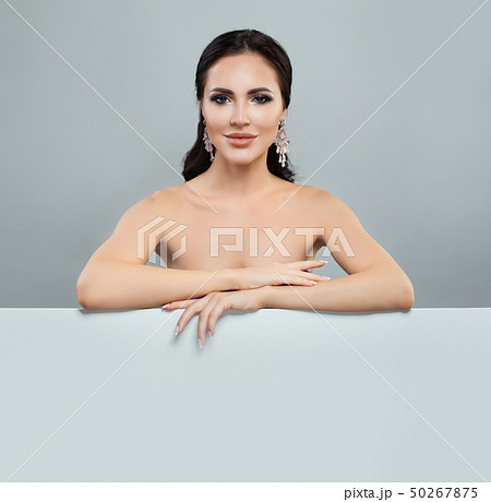 Smiling woman with makeup and jewelry earrings 50267875