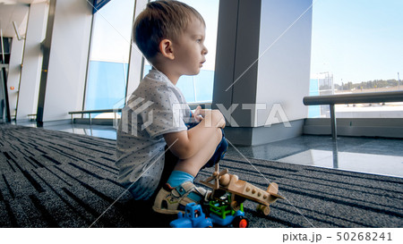 Portrait of little toddler boy waiting for flight sitting on floor at airport 50268241