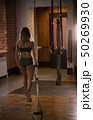 An athlete woman walks away from the gym after the training 50269930