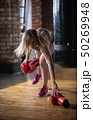A woman boxer puts up boxer gloves from the floor and putting it on 50269948