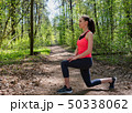 Fitness woman doing front lunge before run in summer forest 50338062
