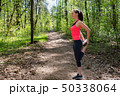 Fitness woman doing leg stretching before run in forest 50338064