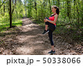 Woman runner doing warm-up exercise before jogging in forest 50338066