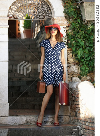 Elegant woman in red hat with suitcase 50382382