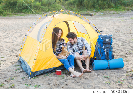Pet, summer tourism and nature concept - young couple sitting with cat near a tent 50389869