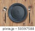 黒い皿とスプーンとフォークと食卓 50397588
