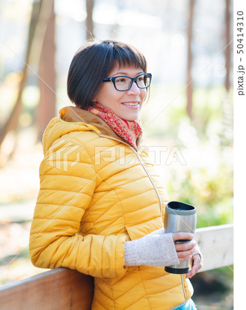 Happy wide smiling women in bright yellow jacket 50414310