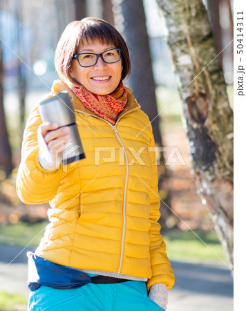 Happy wide smiling women in bright yellow jacket 50414311