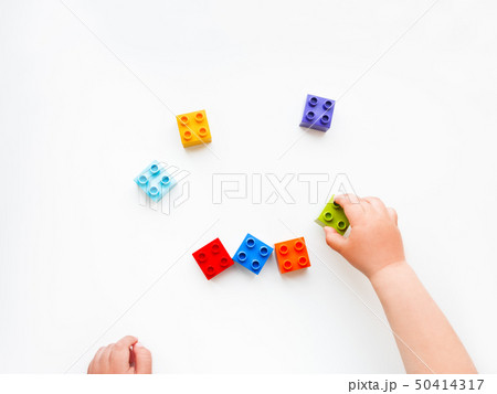 Child is playing with colorful constructor blocks. 50414317