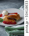 Sliced homemade berry strudel served with fresh red currant berries and powdered sugar on an old 50418633