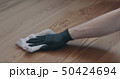 Closeup man in gloves cleaning ash wood floor with wet cloth 50424694