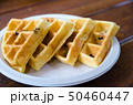 four waffles on plate on wooden table 50460447