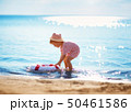 little boy playing at the beach in hat 50461586