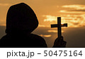 A monk in a hood with a crucifix in his hands stands against the backdrop of a dramatic sky at 50475164