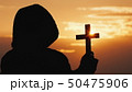 A monk in a hood with a crucifix in his hands stands against the backdrop of a dramatic sky at 50475906