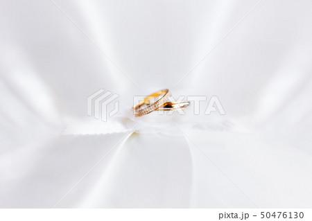 Golden wedding rings with diamonds on white silk 50476130