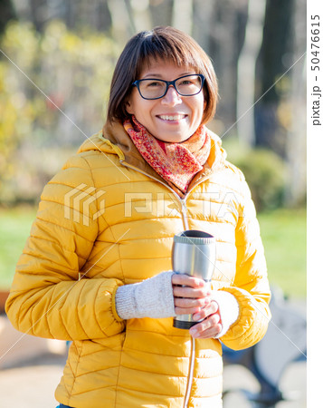 Happy wide smiling women in bright yellow jacket 50476615