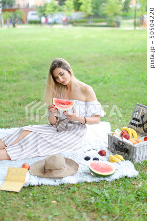 Young girl sitting on plaid near fruits and hat, eating watermelon, grass in background. 50504220