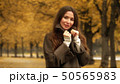 Beautiful young brunette wearing coat looks at the camera on autumn alley 50565983
