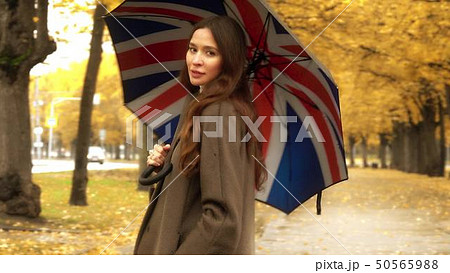 Beautiful young woman standing with umbrella on autumn alley on a rainy day 50565988
