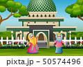 Cartoon muslim women posing in front the mosque 50574496
