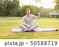 Young happy man taking selfie while doing yoga at the park 50588719