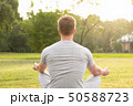 Rear view of young man sitting and meditating at the park 50588723