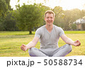 Young happy handsome man smiling while meditating at the park 50588734