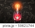 Businessman with light bulb head holding gift box with red ribbon in hands on black question mark 50621744