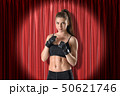 Young athletic girl in black sport clothing ready to fight on red stage curtains background 50621746