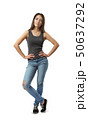 Young woman in gray sleeveless top and blue jeans standing with hands on hips and one leg in front 50637292