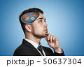 Young businessman thinking with white house, gear wheels, bricks, coil springs in his head on blue 50637304