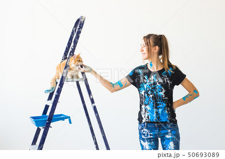 Young woman painter, designer and worker paints the wall. The cat sits next on the ladder and looks 50693089