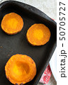 Round pieces of baked pumpkin on baking sheet 50705727
