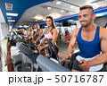 Young sporty people on simulators in a gym 50716787