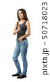 Young woman in sleeveless top and jeans standing in half-turn with left hand in pocket and right 50718023