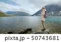 A young woman with a backpack admires the alpine lake in Norway 50743681