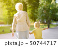 Beautiful granny and her little grandchild walking 50744717