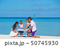 Happy family with map on the beach 50745930
