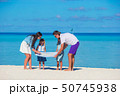 Happy family with map on the beach 50745938